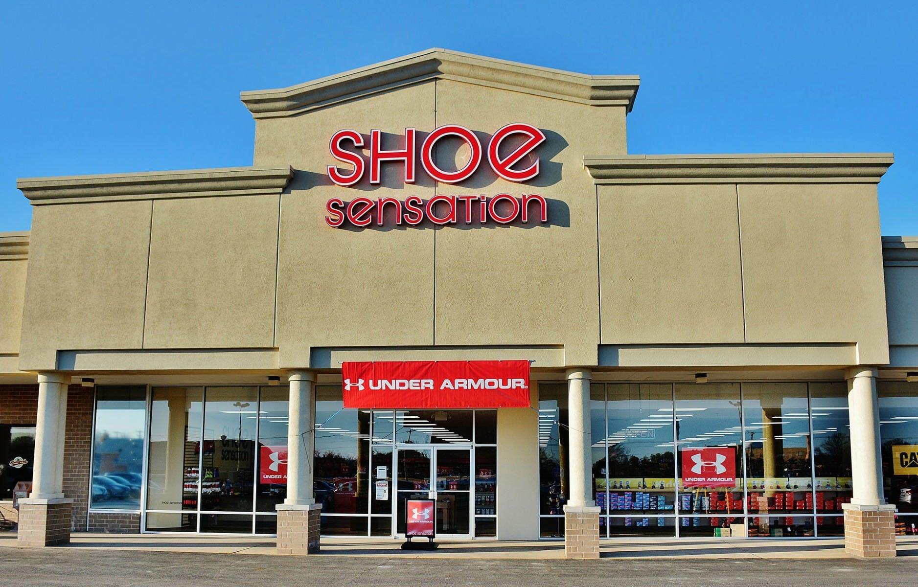 Shoe Sensation storefront with Under Armour sale displays.